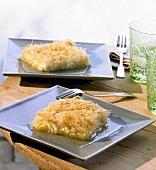Zwei Stücke Künefe mit Sirup auf eckigen Tellern