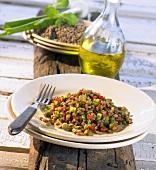A large plate of lentil salad and a bottle of olive oil
