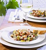 Eine Portion Meeresfrüchtesalat und ein Glas Weißwein
