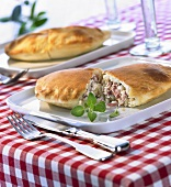 Two halved calzones with ricotta and ham filling