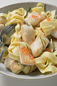 Ribbon pasta with pieces of tilapia fillet in lemon sauce