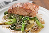 A fried salmon fillet on mie noodles & vegetables (close-up)