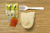 Asian instant noodles with spice mixture & fork on bamboo mat