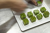 Putting cubes of jellied peas on a plate