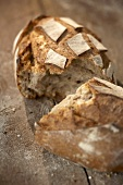A broken loaf of rustic bread on wooden background