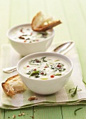 Two bowls of cream of kohlrabi soup with ramsons & white bread