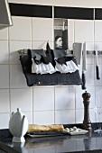 Küche mit schwarzer Arbeitsplatte mit darauf liegendem, frischem Baguette und Küchenutensilien in Schwarz und Weiss