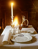 An elegant place-setting with wine, candlelight & open fire