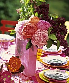 Vase of peonies and lilac on laid table