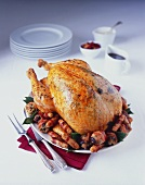 Roast turkey with pistachio stuffing, sausages, bacon-wrapped prunes