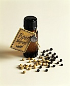 A small bottle of pepper oil and peppercorns