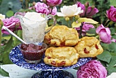 Scones with cherries and whipped cream in garden
