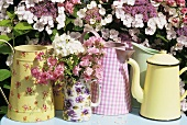 Jugs and pots in front of flowering shrub out of doors