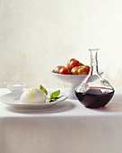 Still life with mozzarella, tomatoes and carafe of red wine