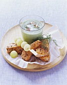 Cold cucumber soup with coriander salmon and melon balls