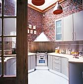 Blick in Küche mit Herd in der Ecke & hohen Ziegelsteinwänden