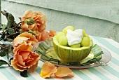 Melonenkugeln mit Sahne in ausgehöhlter Melone, Rosen