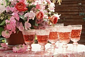 Several glasses of rosé wine with a vase of flowers