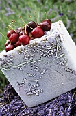 Fresh cherries on block of ice with lavender