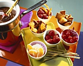 Chocolate fondue with assorted fruit and pieces of cake
