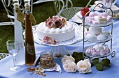 Cakes and liqueur on a table out of doors