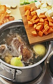 Preparing Tafelspitz (boiled beef): meat & vegetables in a pan