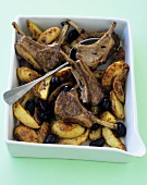 Lamb chops with olives and potatoes in a baking dish
