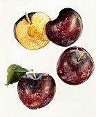 Two whole plums and one halved plum against white background