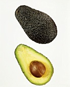 Whole avocado and half an avocado against white background