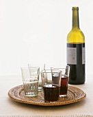 Red wine in bottle and glasses on tray