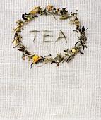 The word TEA in a ring of herbal tea leaves