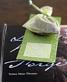 Tea bag lying on book and card