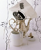 Silver teapot, tea strainer, tea beaker and printed napkin