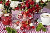Strawberries with sugar and icing sugar on a cake stand with strawberry jam and coffee