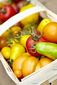 Various types of tomatoes in a wooden basket (close up)