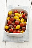 Various types of cherry tomatoes with garlic, thyme and seasalt in a baking dish