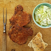 Pork chops with a cucumber-yogurt dip and unlevened bread