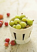 Gooseberries in a wooden basket and on a wooden surface