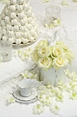 White roses and a white wedding cake made of meringue