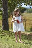 A little girl holding an apple