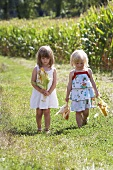 Two girls standing next to a corn field holding corn cobs