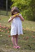 Mädchen isst Maiskolben im Garten
