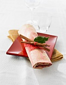A place setting with cinnamon sticks and a holly leaf