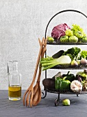 Vegetables on an etagere with wooden salad servers leaning against it and a bottle of oil standing next to it