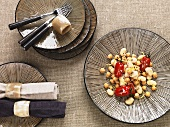 Looking down onto a stripped plate, oriental, with preserved tomatoes and chickpeas