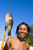 A young man with a speared parrotfish on a beach