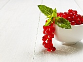Redcurrants and mint leaves in a bowl