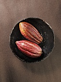 Two cocoa pods in a bowl, seen from above
