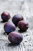 Five plums on a wooden surface