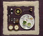 A festive place setting with pea soup and rice pudding framed by grains of rice